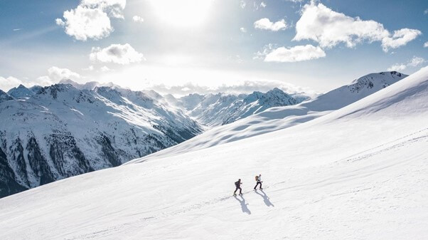 two walkers climbing a mountain in the snow